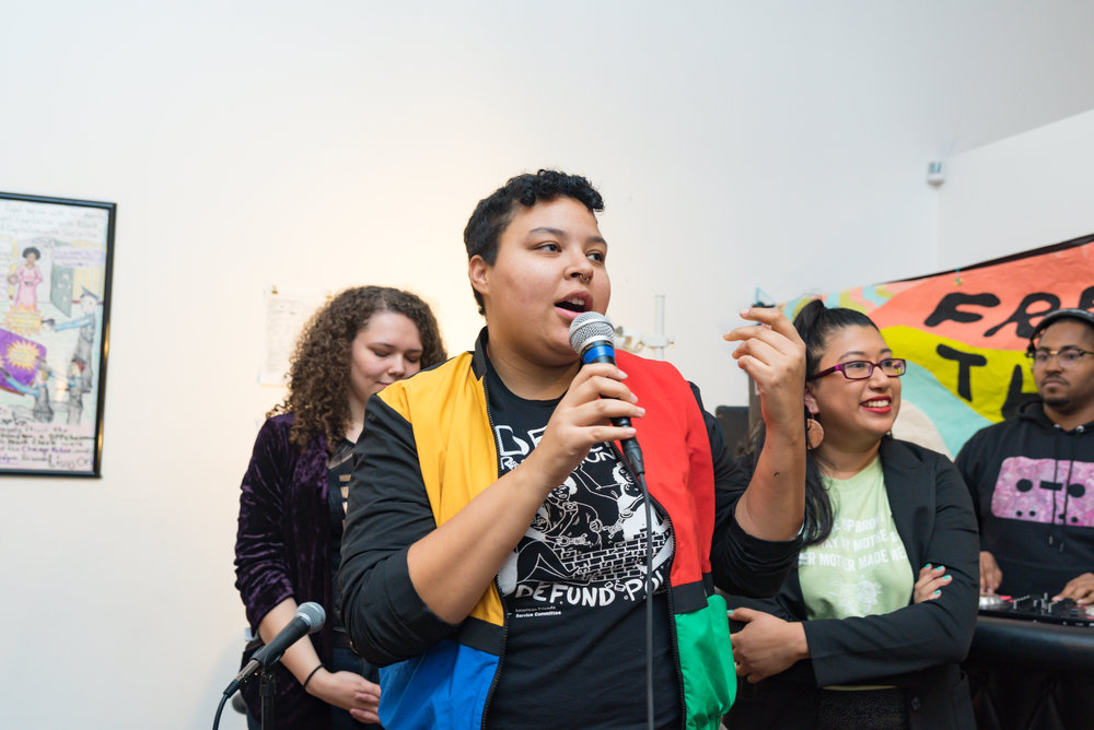 Image: Candid photograph of Darien R. Wendell speaking into a microphone at the For The People Artists Collective Third Annual December Showcase on December 2nd, 2018. They are wearing a black shirt with white letters and a bomber jacket with yellow, red, blue, and green colors on the front. Behind them are people smiling and looking outside of the photo frame. Photo courtesy of Sarah-Ji of Love and Struggle Photos.