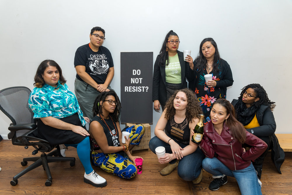 "Image: Photograph of eight members of For the People Artists Collective at their Third Annual December Showcase on December 2nd, 2018. They are all looking directly at the camera while posing around a black poster with white coloring that reads ""Do Not Resist?"". Photo courtesy of Sarah-Ji of Love and Struggle Photos."
