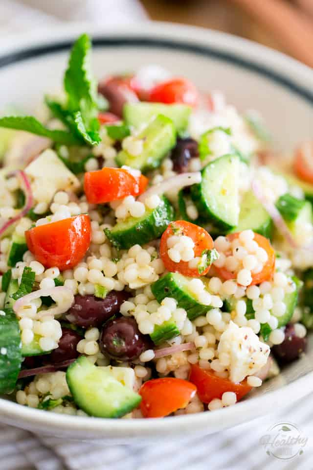 GREEK STYLE COUSCOUS WITH SPINACH, FETA & OLIVES - 1/4 c Garlic Olive Oil2 c pearl couscous2 1/2 c chicken broth2 boneless, skinless chicken breasts4 c packed baby spinach1 bell pepper, seeded and diced1 pint grape tomatoes1/2 c Kalamata olives1 c feta cheese, diced1 tbsp. chopped fresh parsley1 tsp chopped fresh oregano2 tbsp Balsamic Vinegarjuice from 1/2 lemon2 tbsp Lemon Olive OilSea Salt- to tasteHeat the garlic olive oil over medium heat in a large pot. Add the pearl couscous. Toast the couscous until light golden brown, stirring frequently. Add the chicken broth. Bring the mixture to a boil. Add the chicken and stir. Reduce the hear to low, cover and simmer. Cook until the chicken is fully cooked and the pearl couscous is tender, about 10-12 minutes. Add the baby spinach and stir until the spinach wilts. Add the red bell pepper, grape tomatoes, Kalamata olives, feta cheese, parsley and oregano. Stir well. Turn off the heat. Add the balsamic vinegar, lemon juice and Lemon Olive Oil. Season with Sea Salt and Coarse Black Pepper, to taste. Transfer to a serving dish and serve.
