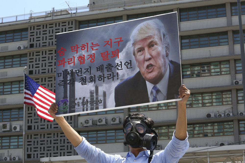 "A South Korean environmental activist wearing a gas mask participates in a protest to denounce the U.S. withdrawal from the Paris climate accord, in front of the U.S. Embassy in Seoul, South Korea, Monday, June 5, 2017. The sings read "" A breathtaking earth and the U.S. withdrawal from the Paris climate accord."" (Photo: AP /Ahn Young-joon)"