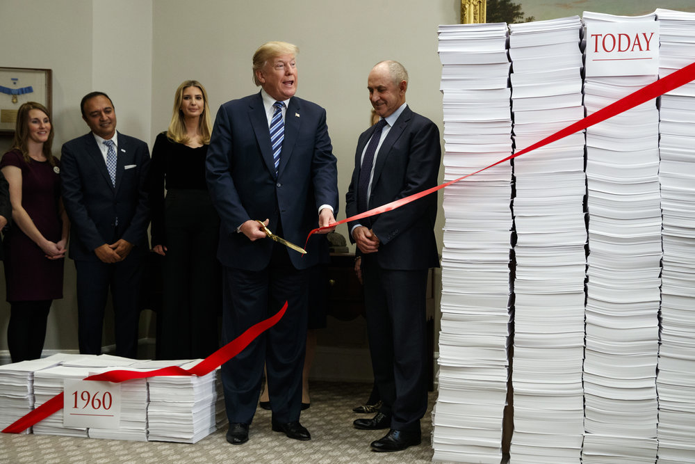 President Donald Trump cuts a ribbon during an event on federal regulations in the Roosevelt Room of the White House, Thursday, Dec. 14, 2017. (AP Photo/Evan Vucci)