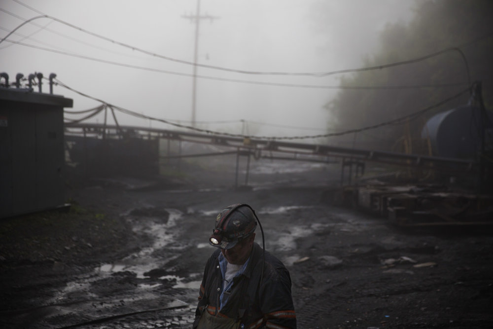 """Coal miner Scott Tiller walks through the morning fog before going underground in a mine less than 40-inches high in Welch, W.Va.In December, the Trump administration announced plans to make """"less burdensome"""" a regulation meant to protect miners' from breathing coal dust that causes black lung disease.(AP Photo/David Goldman)"""