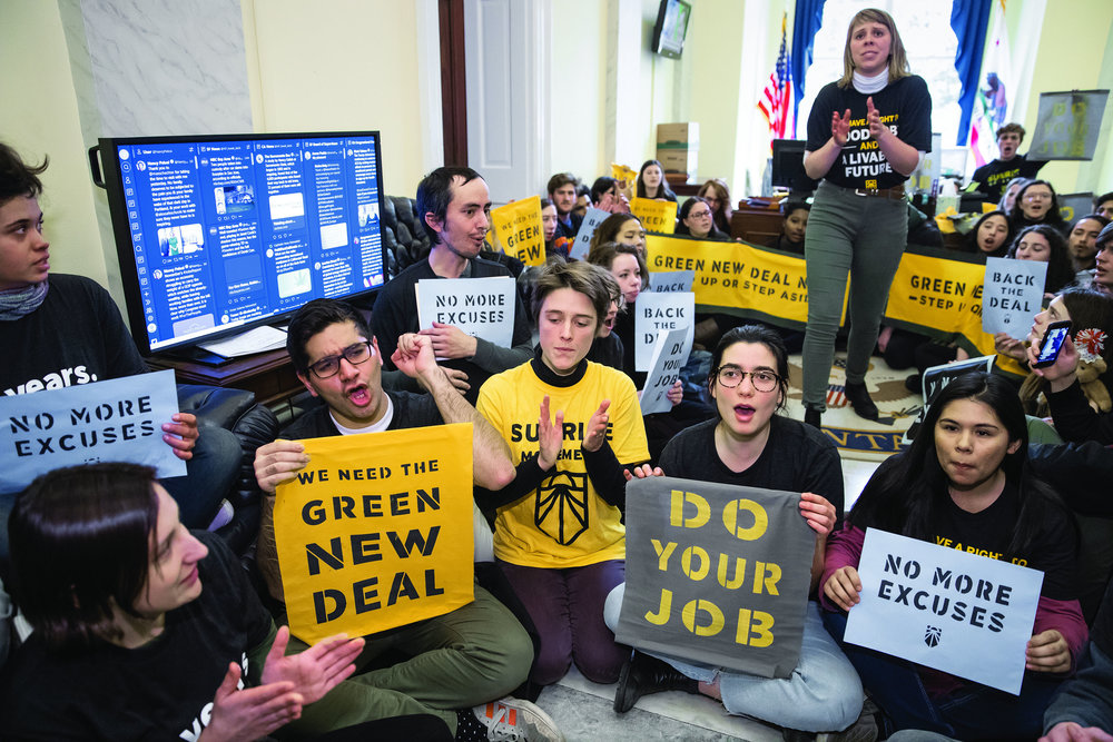 Environmental activists occupy the office of House Democratic Leader Nancy Pelosi of California, the speaker-designate for the new Congress, as they try to pressure Democratic support for a sweeping agenda to fight climate change, on Capitol Hill in Washington, Monday, Dec. 10, 2018. (AP Photo/J. Scott Applewhite)