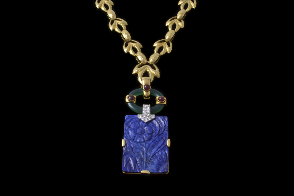 David Webb 18k gold, platinum, chrysoprase, diamond, and ruby pendant, featuring a finely carved lapis panel with floral details, c. 1970's