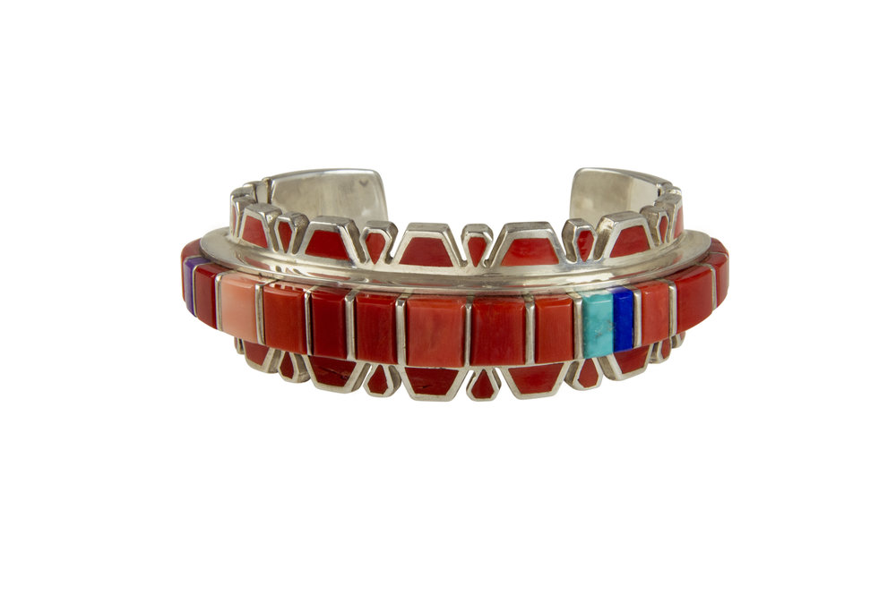 An inlaid coral, turquoise, lapis lazuli, sugilite and silver cuff bracelet, by Vernon Haskie, Navajo.