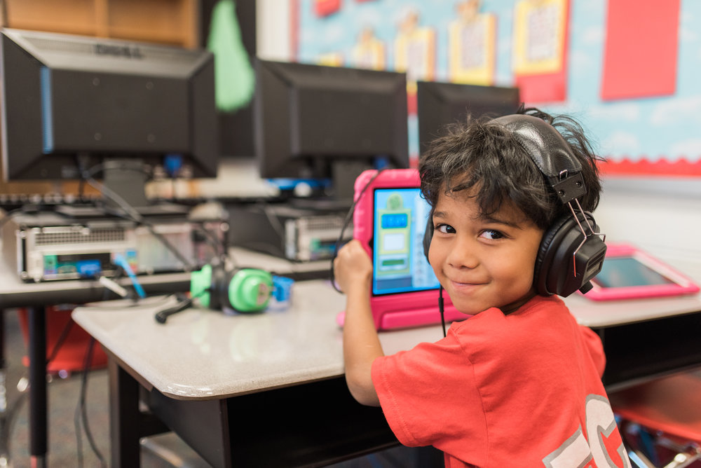 Early Childhood Center student with headphones working on iPad.