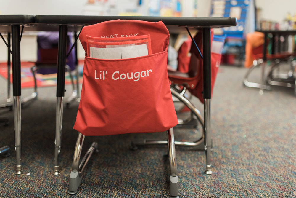 """Lil' Cougar"" seat pocket on back of young students' chair."