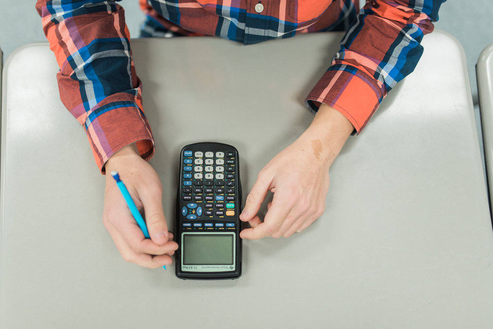 Student sitting at desk, prepared for class with calculator and pencil.