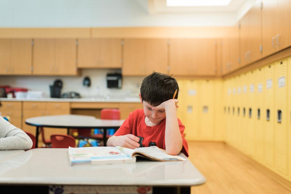 Elementary School student sitting at desk working in workbook.
