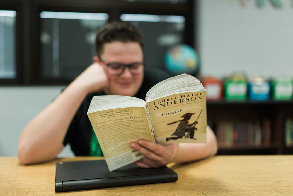 Middle School student reading a book.