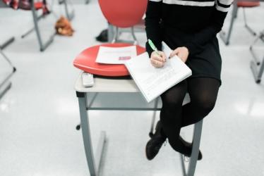 Teacher sitting on edge of desk grading a paper.