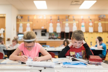 Elementary School students working in their workbooks during class.