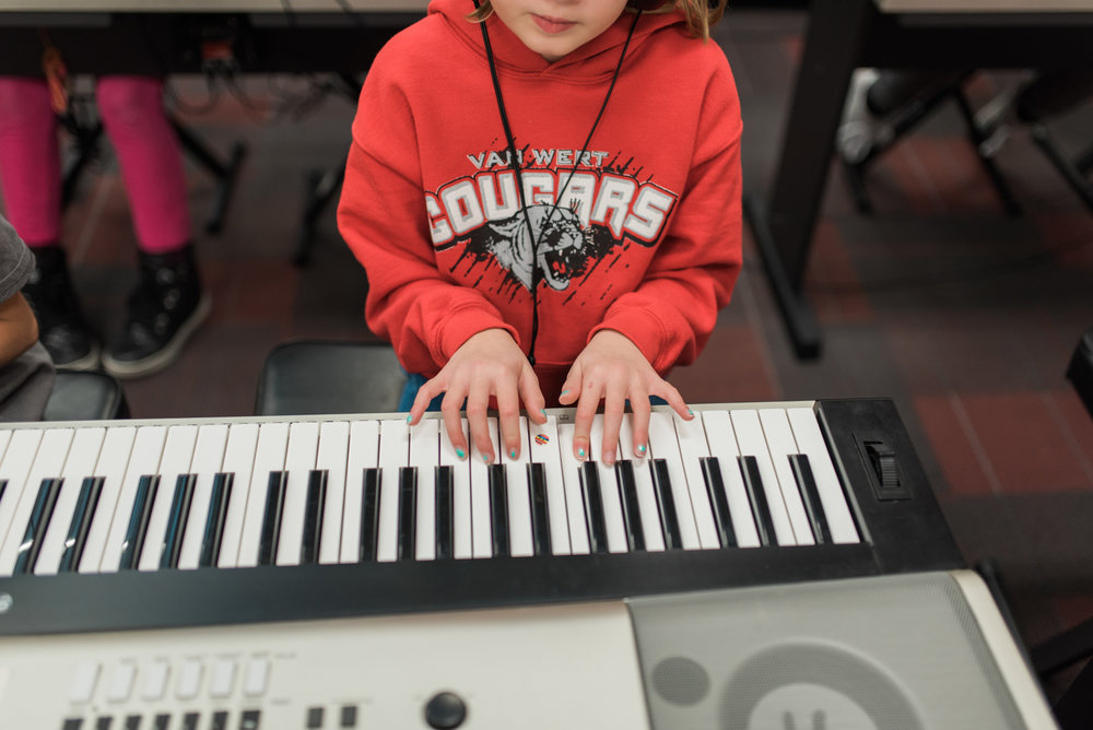Elementary School student learning to play piano.