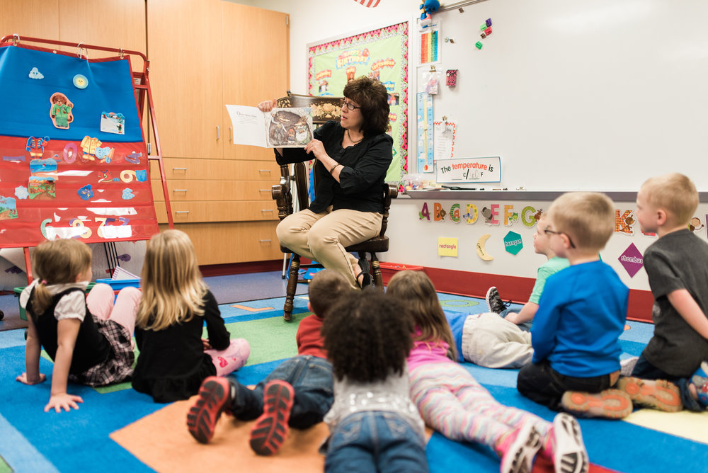 Early Childhood Center teacher reading to a group of children.