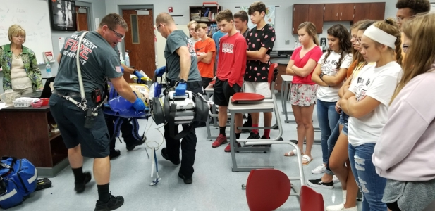 VWHS students look on as Van Wert Fire & EMS first responders provide first aid during a simulation.