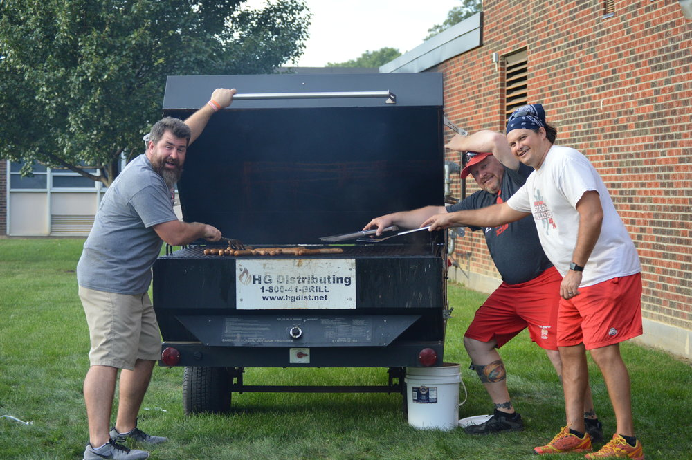 Teachers grilling burgers and brats at the scholarship supper