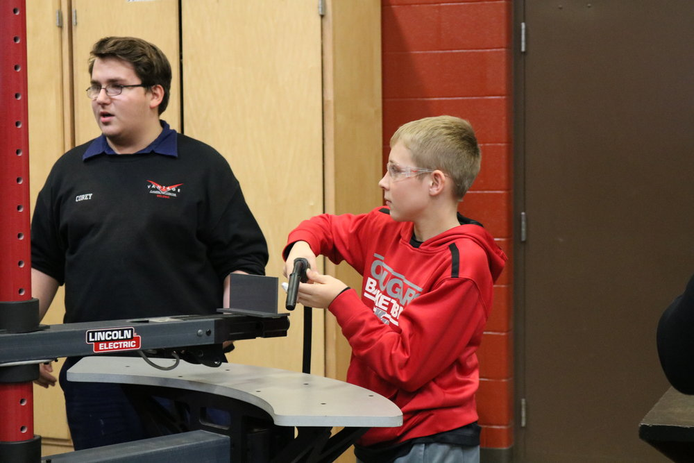 A VWMS 8th grader practices welding under the supervision of a Vantage student.