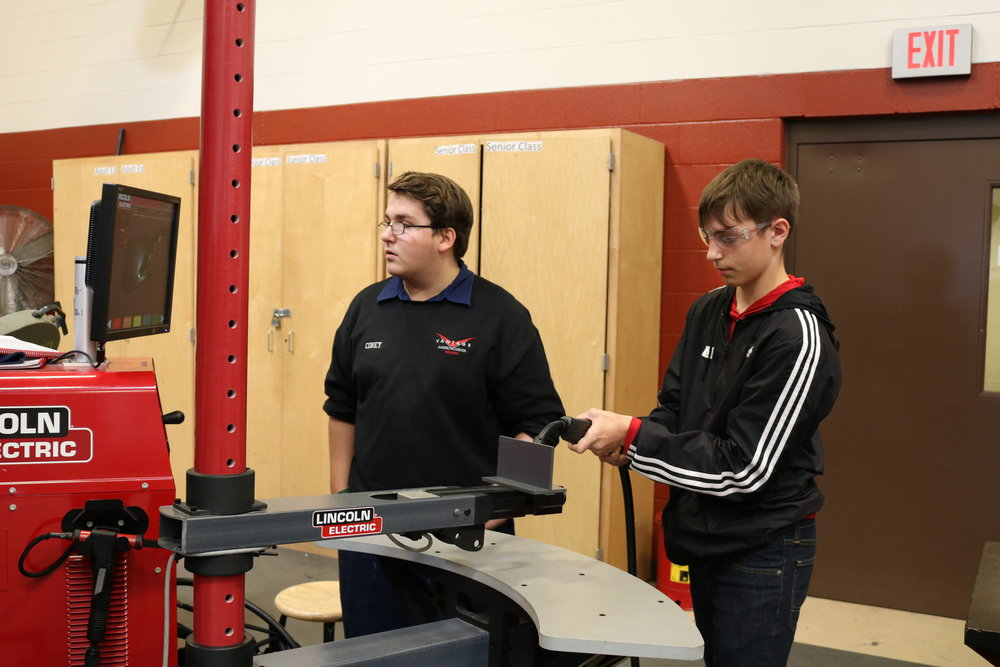 A VWMS 8th grader practices welding while a Vantage student looks on.