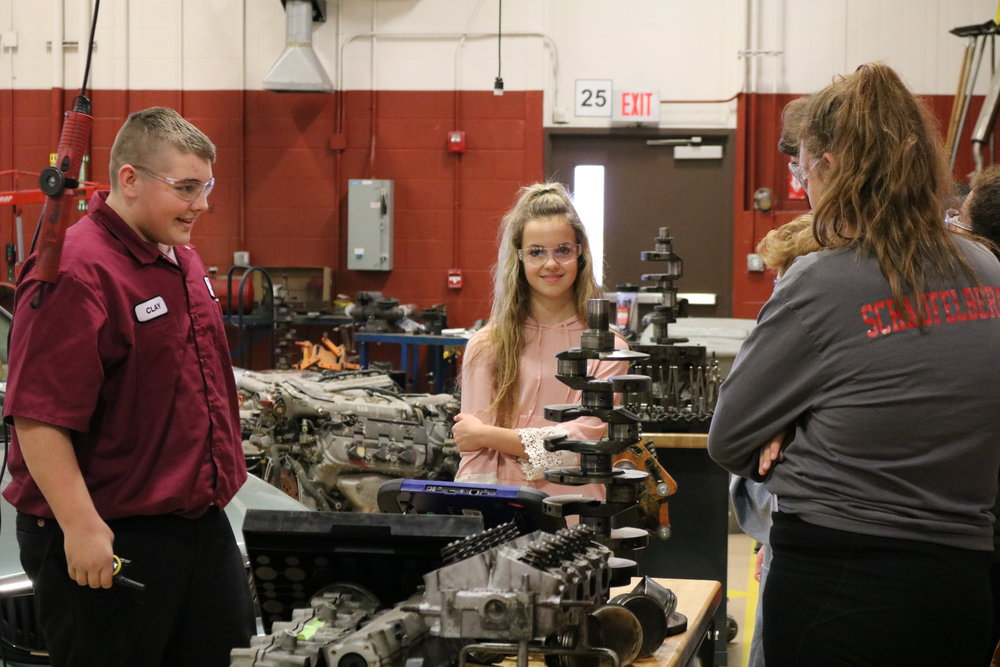 VWMS 8th graders check out a car engine while a Vantage student explains the auto technology program.