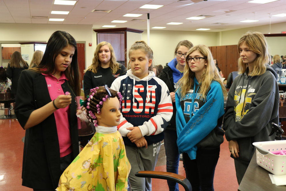 VWMS girls watch as a Vantage student practices her cosmetology skills.