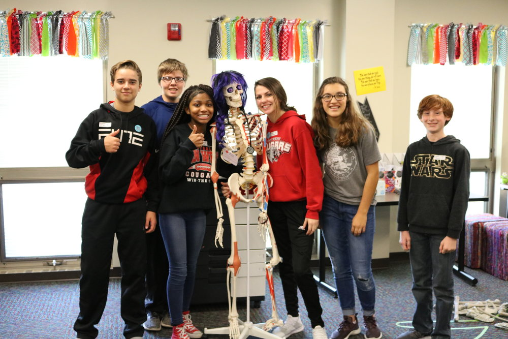 Students post with a skeleton in Vantage's Health Technology program.