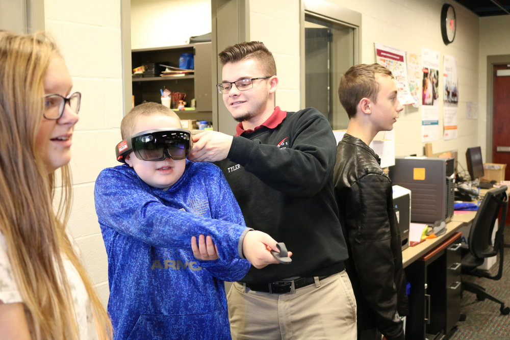 A student plays a game using a virtual reality headset.
