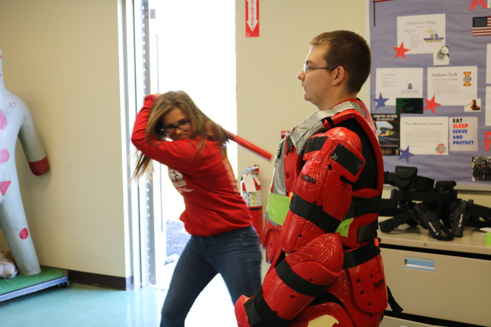 A student takes a swing at a Vantage student dressed in protective material during the Criminal Justice program tour.