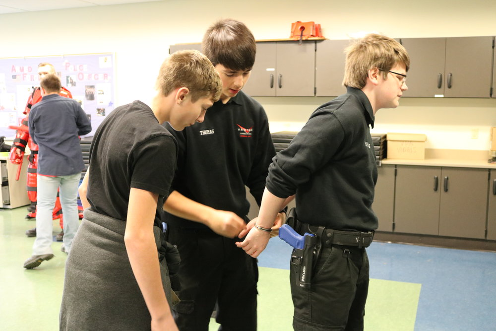 "An 8th grader watches as students practice handcuffing a ""criminal"" at the Vantage tour."