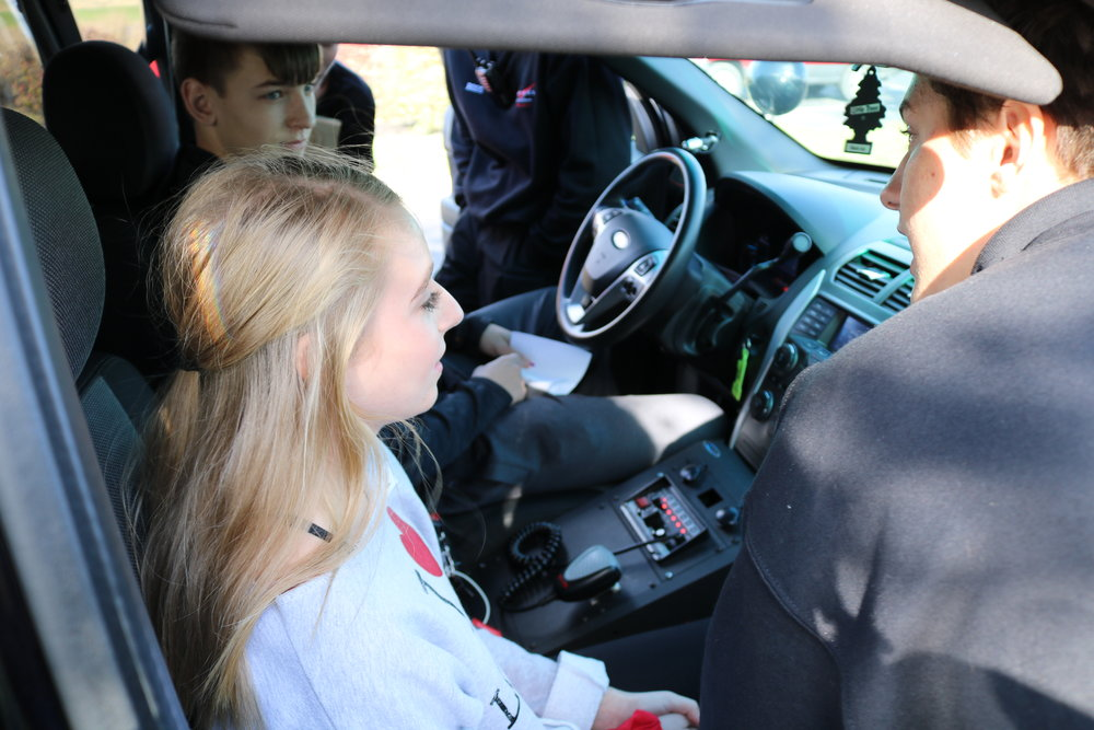 8th grade students sit in the front seat of a patrol car.