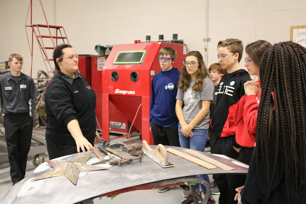 8th graders look on as a Vantage student explains the auto body program.
