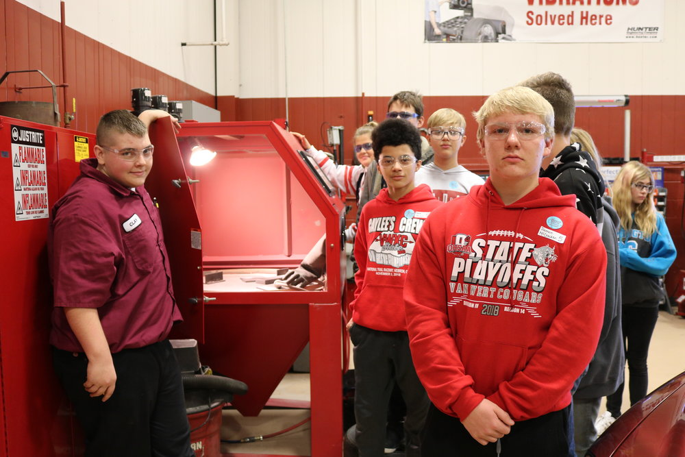 8th graders pose with a Vantage student next to a sandblaster.