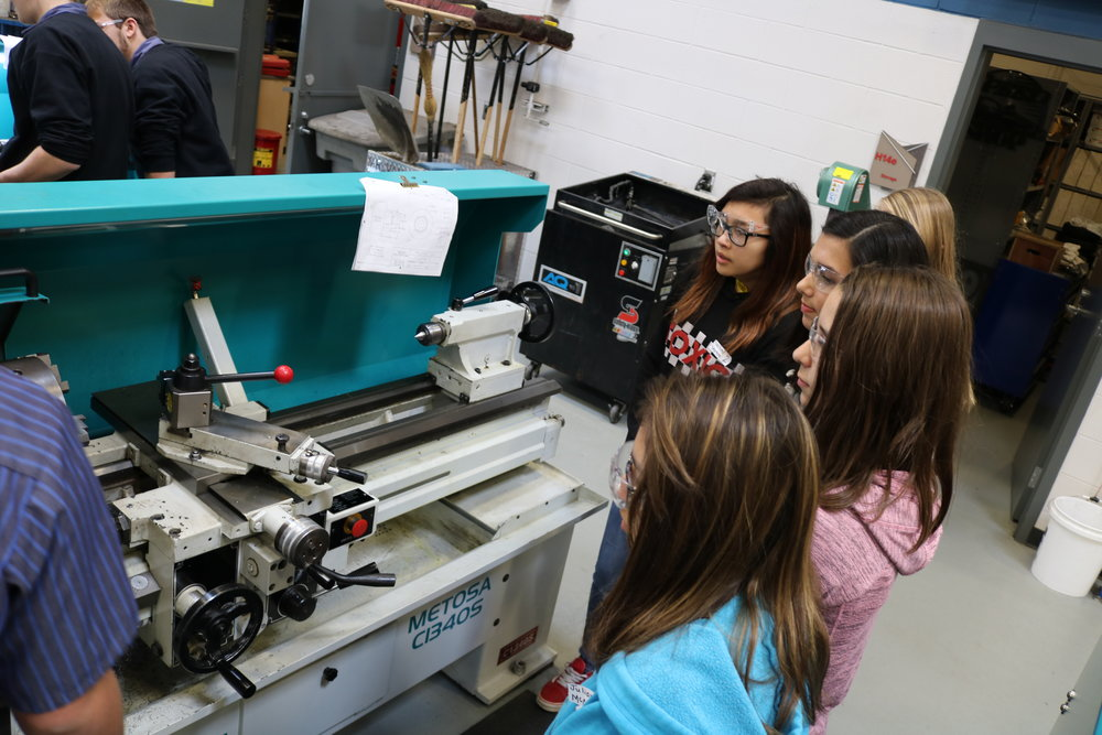 8th grade students watch a machine demonstration.