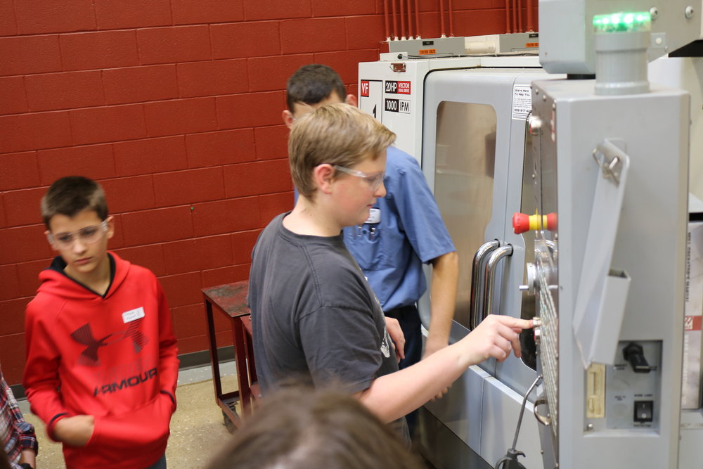 "A VWMS 8th grader hits the ""start"" button on a machine."