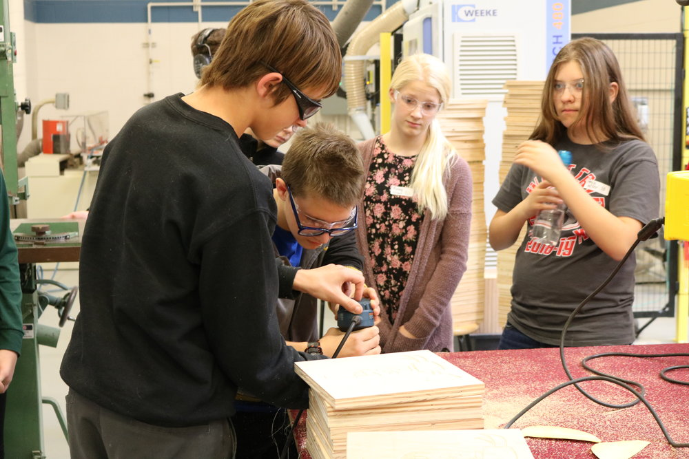 A VWMS 8th grader tries to sand a block of wood for the first time.