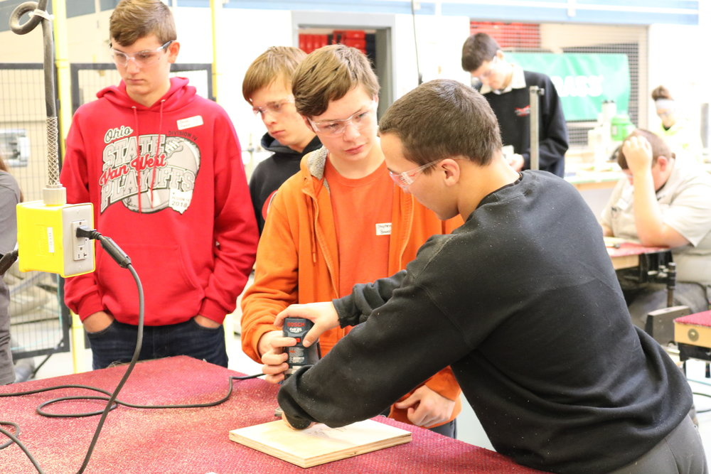 A Vantage student helps a VWMS 8th grader sand a block of wood.