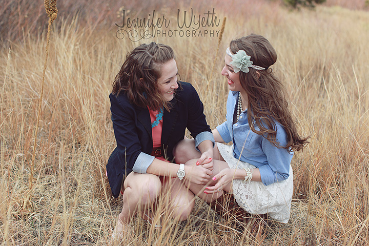 twin girls in dresses giggle together in a field of wheat.