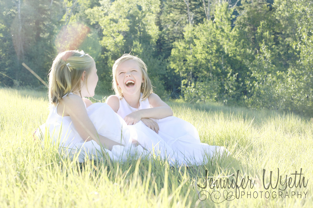 identical twins sit laughing together in grassy field