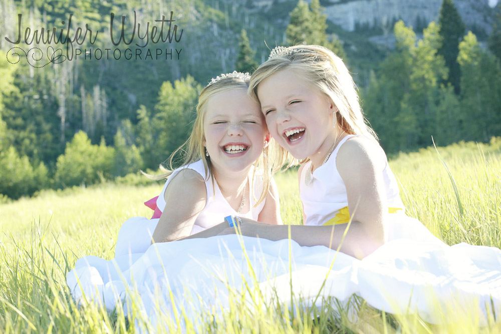 sweet identical twins laughing in their baptism dresses together