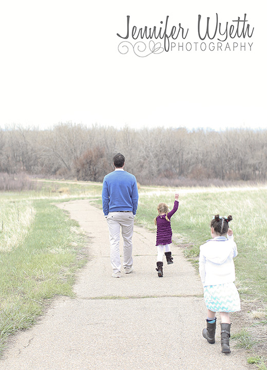father daughters skipping along a path in denver