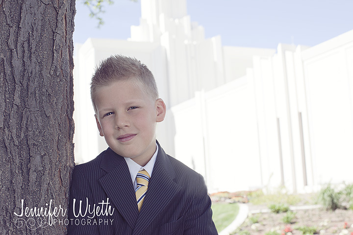 Boy leans against tree in the shade outside of Denver LDS temple
