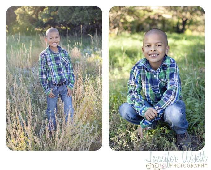 kid crouching in grass and smiling for the camera