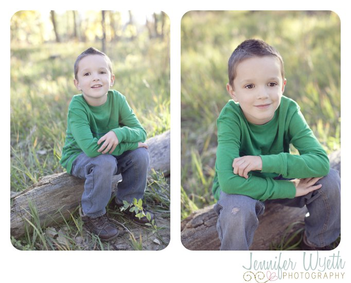 5 year old boy sits on a log in the forest and smiles for the camera