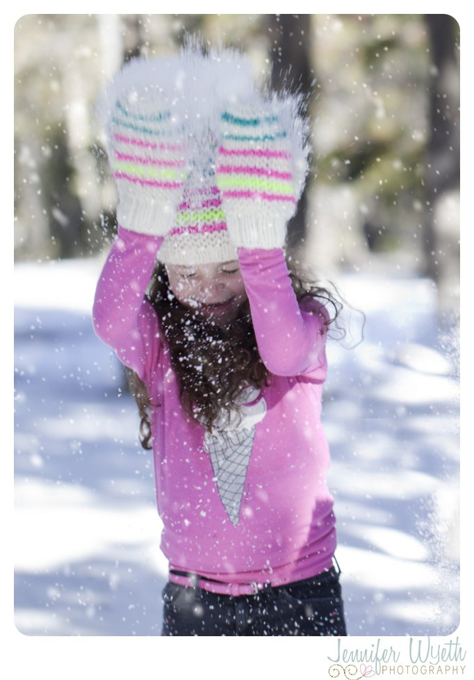 little girl ducking for cover while throwing snow over her head