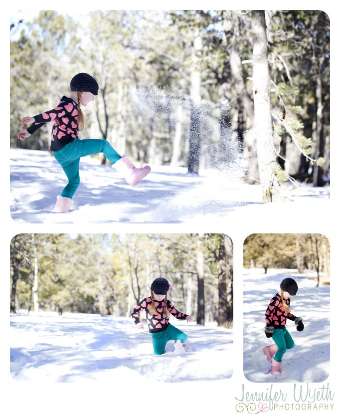 little girl kicking snow in pink boots in the forest