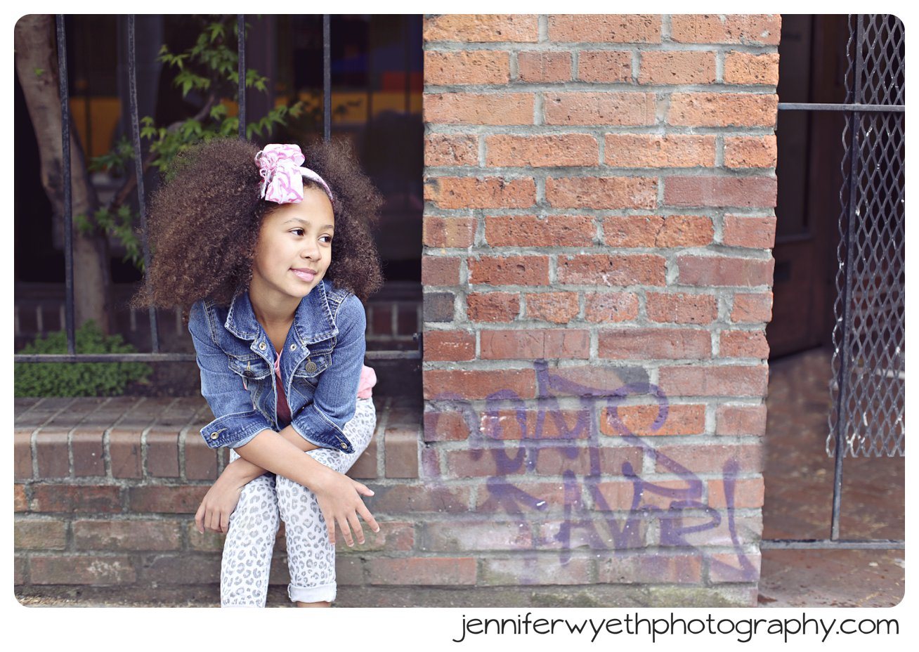 graffiti brick wall that little girl is sitting on for pictures