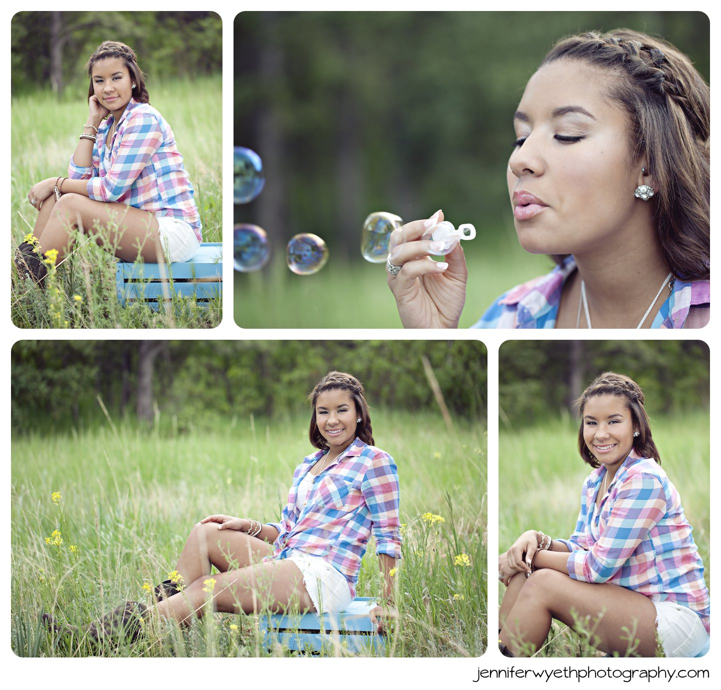 girl sits on blue crate and smiles while she blows bubbles.