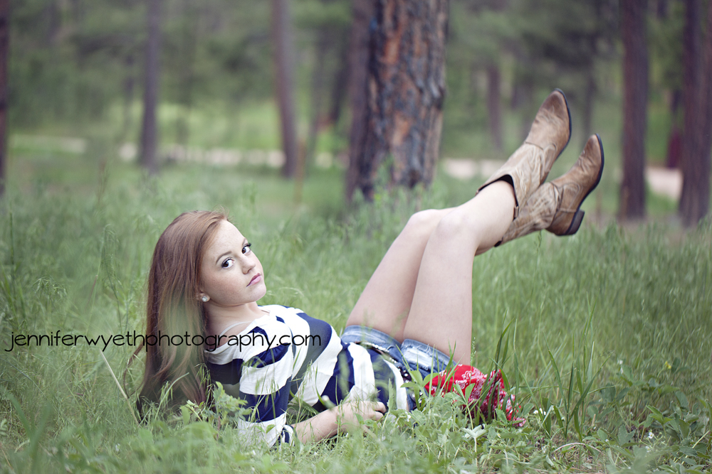 laying in tall grass with legs in air teenage red head has serious look