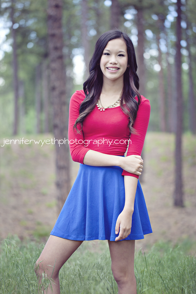 red shirt and blue skirt beautiful asian cheerleader holds one arm with the other hand