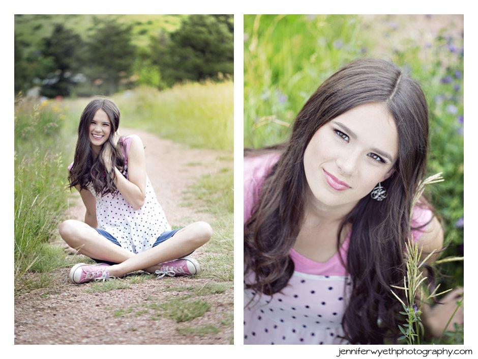 cute girl giggles while sitting on a dirt path by a field