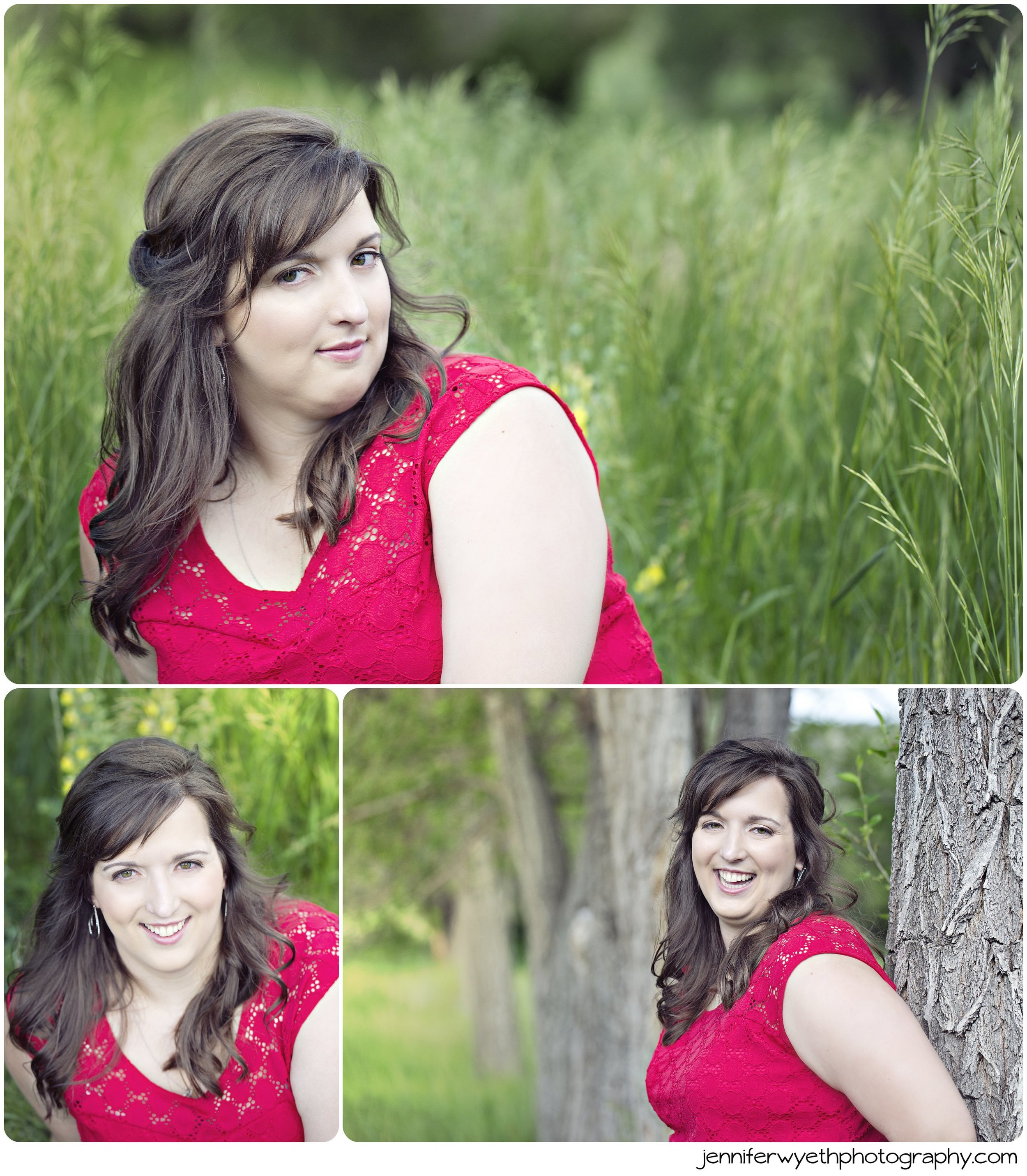 Leaning against a tree a brunette smiles in a red shirt